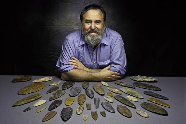 Smithsonian Institution National Museum of Natural History Department of Anthropology crurator Dr. Dennis Stanford sitting in front of several Clovis Points