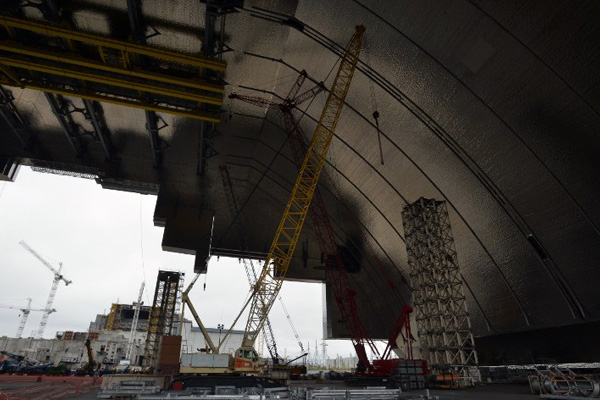 A general view taken on April 26, 2016 shows the construction site of the New Safe Confinement structure (NSC) in front of the shelter and containment area built over the destroyed fourth block of the Chernobyl nuclear power plant. Ukraine marks 30 years since the world's worst nuclear accident at Chernobyl killed thousands and forced a global rethink about the wisdom of relying on atomic fuel. / AFP PHOTO / Genya Savilov
